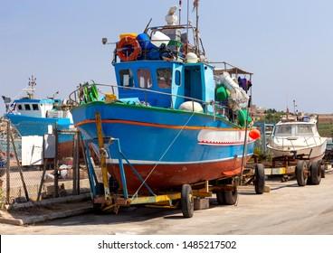 Big blue fishing boat on a cargo cart. Marsaxlokk. Malta.