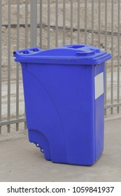 Big blue garbage can near gray fence
