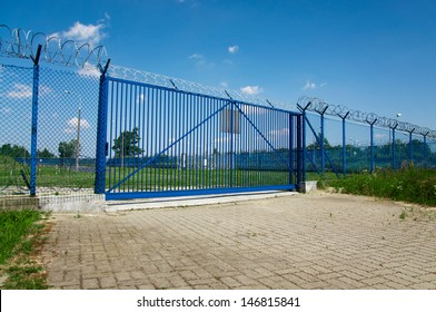 big blue gate with barbed wire