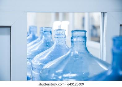 Big blue plastic bottles on  washing conveyor. Close up.