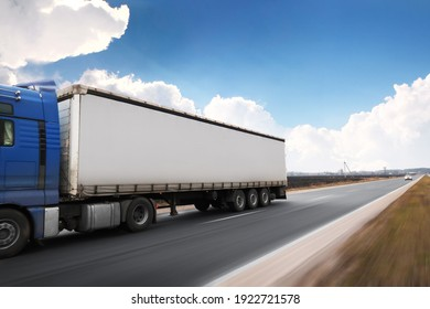 A big blue truck driving fast with a grey trailer with a space for text on a countryside road with other cars against a blue sky with clouds