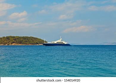 Big blue yacht in blue ocean with blue sky. Corfu. Greece. Ionian island.