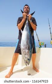 big Bluefin tuna catch by fisherman on boat trolling posing on deck