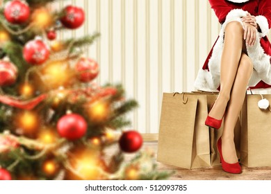 big blurred xmas tree with orange light and woman slim long legs with red heels