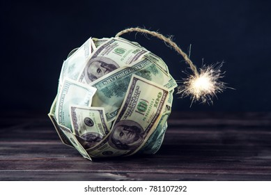 Big bomb of money hundred dollar bills with a burning wick. Little time before the explosion. The concept of financial crisis