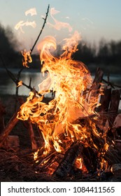 big bonfire with smoke. Flames of a campfire at the sunset&lake background.