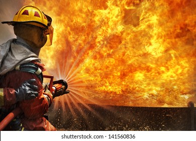 Big bonfire in training. Firemen using extinguisher and water from hose for fire fighting at firefight training of insurance group. Firefighter wearing a fire suit for safety under the danger case.