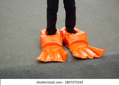 Big boots for a fun run. Doll shoes. Running with uncomfortable shoes. Funny orange rubber flippers.