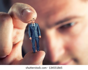 Big boss looking at small businessman in hand