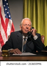 Big boss president calling behind desk with american flag in the background.