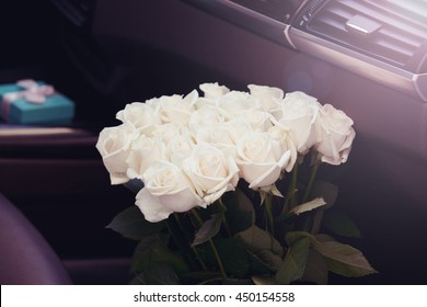 Big bouquet of beautiful fresh roses in luxury car. Romantic concept.