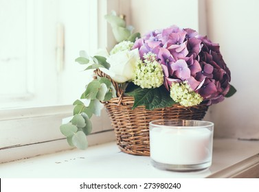 Big bouquet of fresh flowers, purple hydrangeas and white roses in a wicker basket on a windowsill, home decor, vintage style