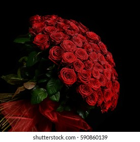 Big bouquet of one hundred big red roses flowers on black dark background