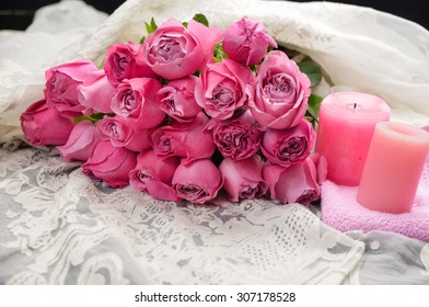 Big bouquet roses lying on with candle on silk