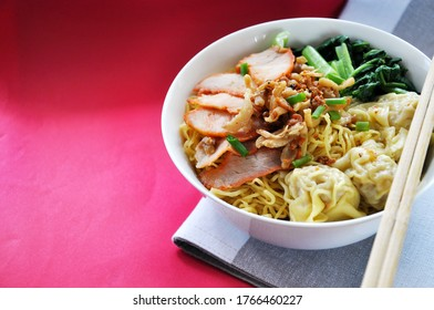 Big bowl of egg noodles with wonton and sliced grilled pork on red background with copy space