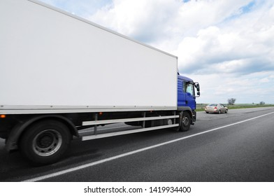 A big box truck with space for text and family car on the countryside road against a cloudy sky