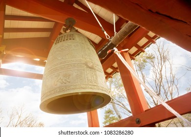 Big brass Buddhist bell and timber knock of Japanese temple in red pavilion on bright blue sky with sun and lens flare background.
