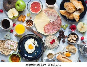 Big breakfast for the big family on the white rustic table.