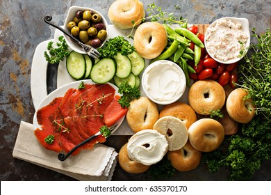 Big breakfast platter with cream cheese, bagels, smoked salmon and vegetables