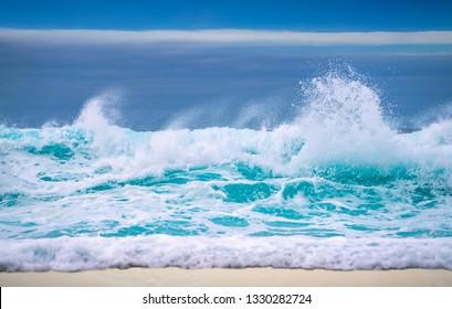 Big breaking Ocean wave on a sandy beach on the north shore of Oahu Hawaii