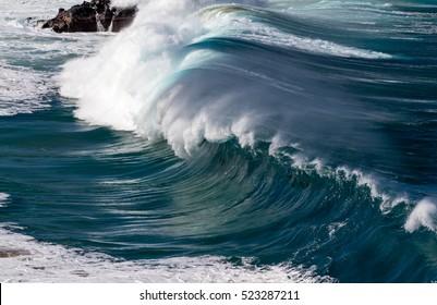 Big breaking Ocean wave on the north shore of Oahu at Waimea bay in Hawaii