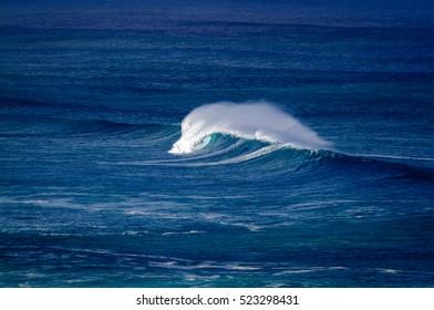 Big breaking Ocean wave on the north shore of Oahu near Waimea bay Hawaii