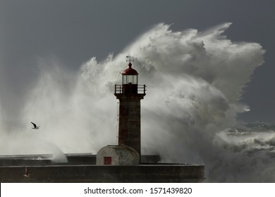 Big breaking sea waves over Douro river mouth old pier and lighthouse