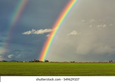Big, brilliant, double rainbow over a green field with a red barn in the distance.  The rainbow and stormy sky are the focal points.