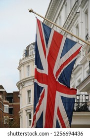 Big British flag on a pole hoisted in the street on house facade during BREXIT negotiations by prime minister Theresa May, London, UK. National emblem, flag of England as a monarchy called Union Jack
