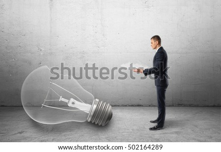 Big broken bulb fallen to the floor and a businessman holding a piece of it on a gray background. Rejected startup idea. Dashed dreams and failed plans. Losing inspiration.