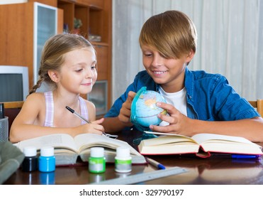 Big brother helping little girl to do homework at home