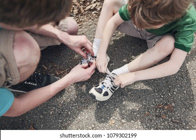Big brother helping little brother tie his shoes