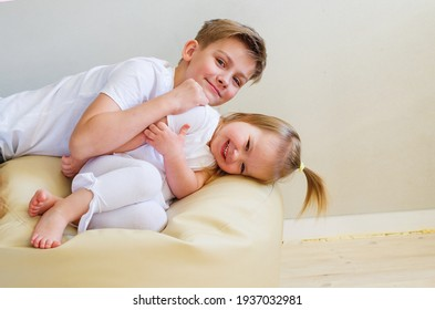 Big brother and his cute little sister laying togetherness fun at home. Two Caucasian siblings brother and sister. Restless cheerful kids in casual clothes playing, having fun, hugging, smiling