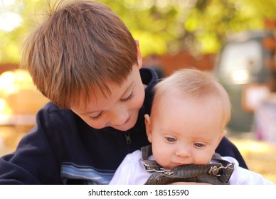 Big brother holding his baby brother at a farm