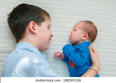Big brother hugging his newborn baby. Toddler kid meeting new sibling. Cute boy and new born baby girl relax in bedroom. Family with children at home. Love, trust and tenderness