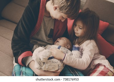 big brother and sister playing with baby brother at home