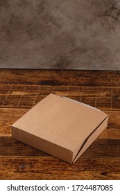 Big brown paper box isolated on wooden background. Eco-friendly disposable food packaging. Preserving nature and recycling concept.