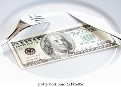 Big bucks/ One hundred american dollars bill on a white plate, with fork and knife. Buying power, money management, charity events & other in business, economy, finance, banking and everyday life.