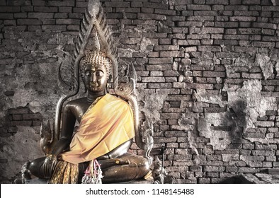 Big buddha statue at Brick wall background. Metal sculpture, Buddha statue to worship.
