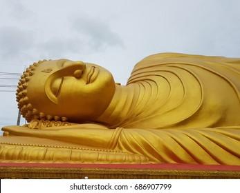 Big Buddha.Huge golden sleeping  Buddha in Thailand. Beautiful big golden Buddha statue on the platform Thailand. Huge golden Buddha statue with blue sky background.