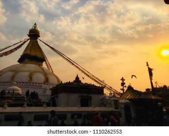 Big buddhist stupa in Katmandu with people walking around,  in the background the sky and the sun with warm colors showing almost the sunset. The picture was taken March 20th, 2018.