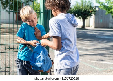 Big bully boy harassing younger kid. Grabbing schoolbag.