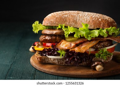 Big burger with bacon, cutlet and mushrooms