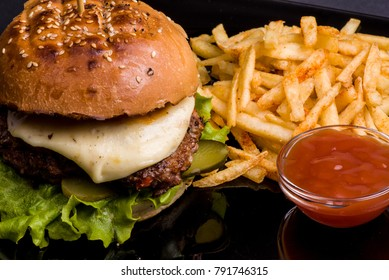 Big burger with beef cutlets, red sauce and rosy french fries on black glass plate