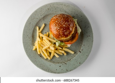 Big burger with french fries on plate isolated on white background, fast food photo for menu cafe or restaurant. Flat top view, overhead.