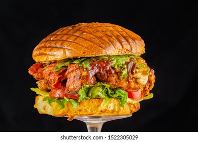 big burger. Hamburger shot on a black dark background, with sausage, sausage, meat, herbs, lettuce, parmesan cheese, onion rings, bacon, human hand, chicken egg, pineapple isolated background