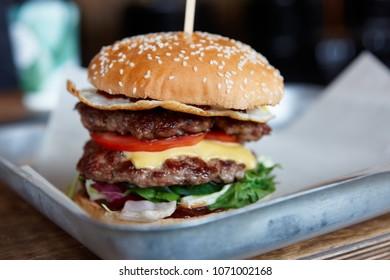Big burger on restaurant table, close-up, focus on the bun