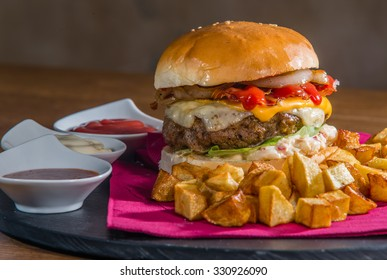 Big burger served for eating. Burger contains lots of extras cheese, bacon, onion, ketchup, lettuce, mayonnaise.