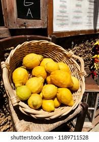 Big busket with yellow lemons on the street