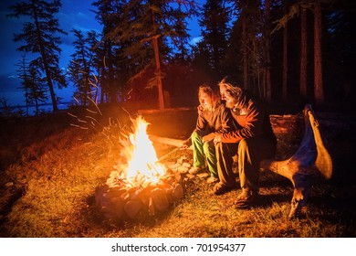 Big camping fire with couple of tourist at night, forest in north Mongolia